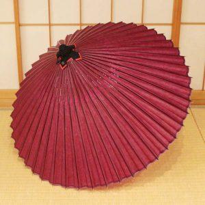 赤紫色の和傘、実際に雨の日に使用できます。熟練の職人により手作業で製作しています。