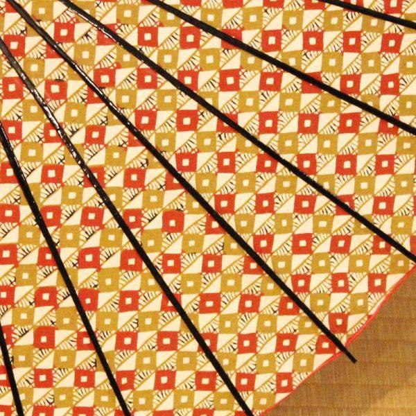 日本における多彩な染色技法の中でも古い伝統を持つ『型染め』、豊かな文様表現と日本人特有の繊細な手技が集約された技法を使った型染和紙を用いた美しい和日傘です。算盤縞と呼ばれる朱色と黄色の菱つなぎのもようが全体に入っています。