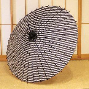 紺と白の縞模様の和日傘、型染和紙、竹、木を主な材料として日本の職人が手作り品。