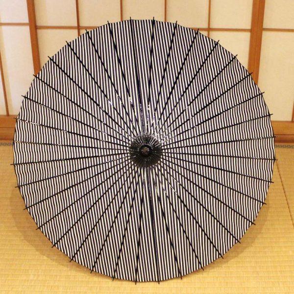 紺と白の縞模様の和日傘、型染和紙、竹、木を主な材料とした日本の職人の手作り品。