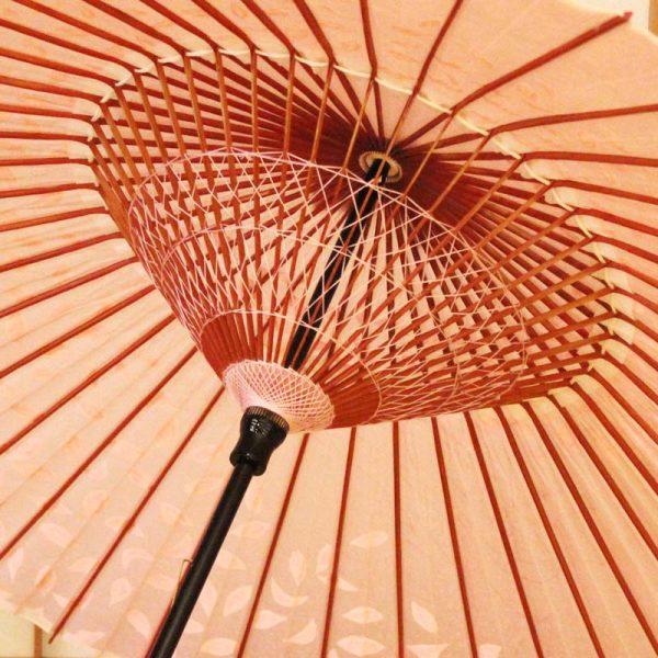 桃色の和傘に手書きで桜吹雪を傘全体に散らしています。雨傘です。