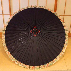 紫色のふちに華扇の飾りもようがある蛇の目傘