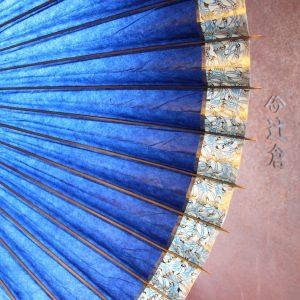 藍色地のふちにさざ波模様のかざりのついた蛇の目傘です。