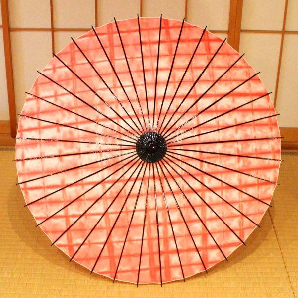 国産の自然素材のみで仕立てた絞り染めの紅色の和日傘です。