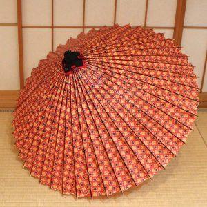 『赤地花菱』は、赤地に花菱紋を全体にあしらった蛇の目傘です。お召し物を選ばず使いやすい文様の和傘です。