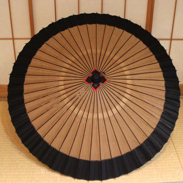 越中の手漉き和紙を使用した光悦茶と黒の二色切り替えの蛇の目傘です。 色合わせにより表情が変わり、お召し物に合わせてお持ちいただきたい粋でモダンな和傘です。