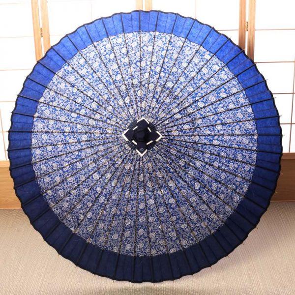 主に竹と和紙で作った雨の日の青色の牡丹唐草もようの和傘です。