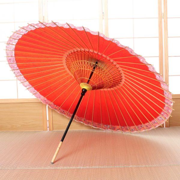朱赤色の和傘。ふちには紅葉の模様があります。