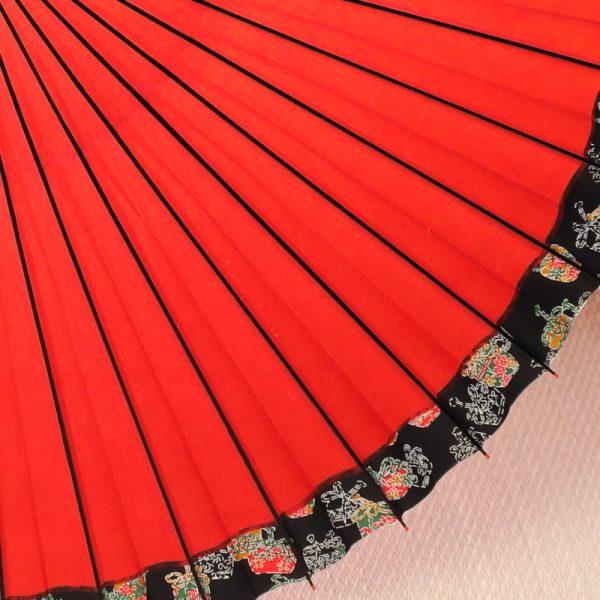 朱赤色の和傘。ふちには縁起の良い宝袋の模様があります。